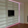 Meuble bibliothèque de grande taille. Le meuble comprend des étagères et d'une porte pour cacher la TV. Eclairage Led sur le pourtours du meuble.
