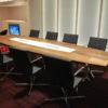 une table de réunion de grande taille en placage bois de type chêne pour une salle de réunion d'une grande entreprise.
