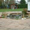 terrasse ronde en bois foncé avec un étang au milieu et une cabane de jardin derrière