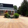 terrasse en bois claire arrondie avec un buisson au centre