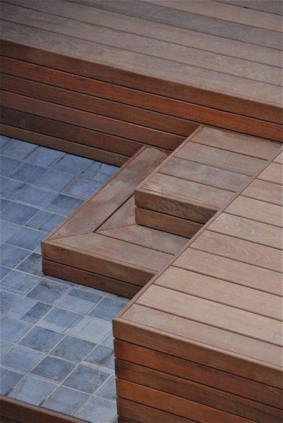 Terrasse en bois et pierre avec escalier contre un mur à Wavre le bois utilisé est de l'ipé de l'éclairage y est intégré