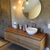 Villa contemporaine avec meuble de salle de bain suspendus design en chêne massif avec miroir rond et vasque à déposer.
