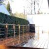 terrasse en bois devant une maison contemporaine garde-corps en inox et bois