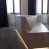 un ilot central aux formes contemporaines dans un dressing avec moquette et portes invisibles.